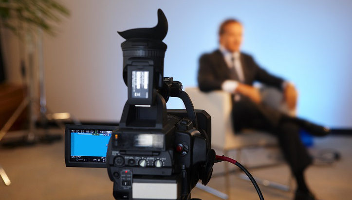 Television interview program with selective focus on camera screen copy space